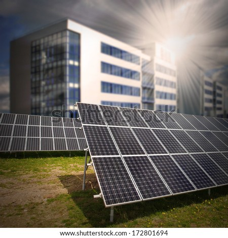 Solar panels against modern passive house. Sustainable development and renewable resources concept.  - stock photo