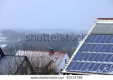 solar panels and a smoking chimney in winter season - stock photo