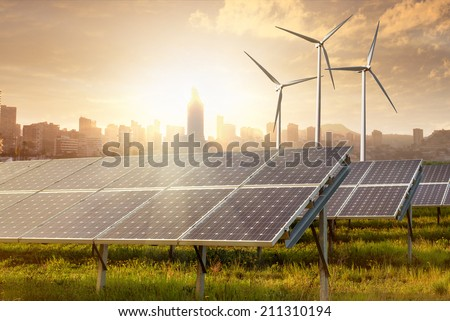 solar panels and wind generators against city view on sunset - stock photo