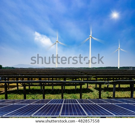 solar panels and wind generators under blue sky on sunset