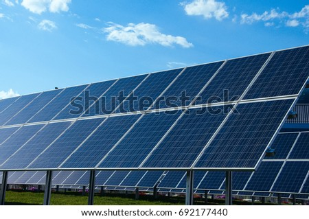 Solar panels, blue sky and green grass