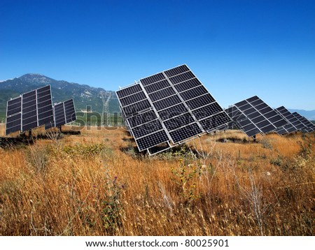 solar panels deployed on a field under the mountain Olympus in Greece - stock photo