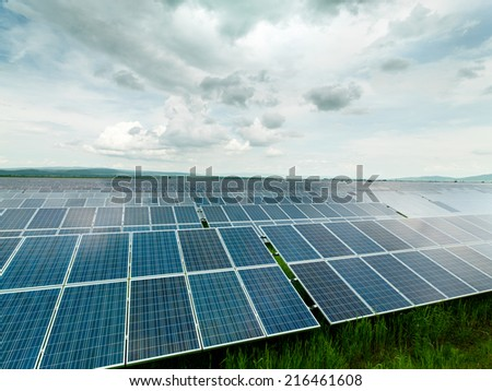 solar panels displayed on a green field, with clouded blue sky - stock photo