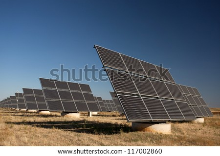 Solar panels in a greenfield, over blue sky - stock photo