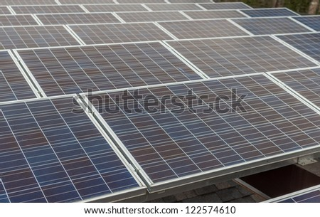 Solar panels in a industrial photovoltaic system installed on the roof of a shed - stock photo