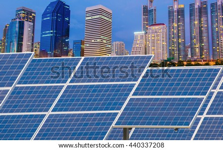 Solar Panels in front of modern office building at Night. - stock photo