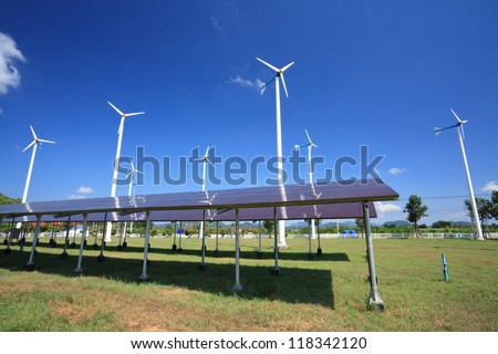 Solar panels in front of wind energy plants