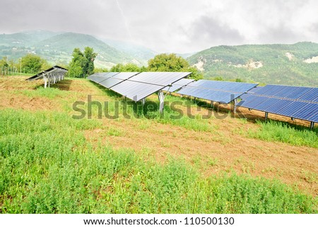 solar panels in mountain under cloudy sky - stock photo