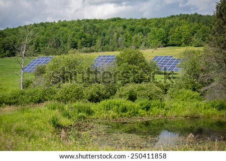 Solar panels in the field, trees and small pond in background - stock photo