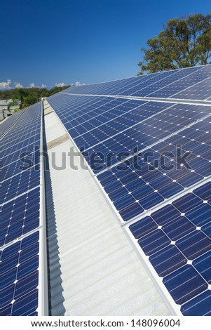Solar panels in the sun on large roof - stock photo