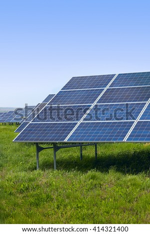 Solar panels on a green field on a sunny day - stock photo