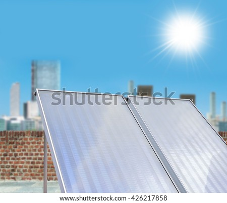 Solar panels on a house to heat water and light supply with blue sky background - stock photo