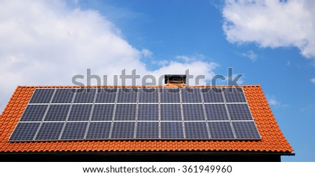 Solar panels on a residential house roof. Typical view of a traditional tile roof modernized with elegant high-technological equipment for renewable energizing of  building.  - stock photo