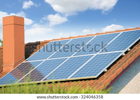 Solar panels on a roof of a house against blue sky - stock photo