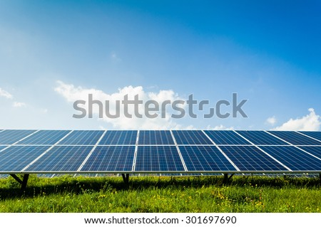 Solar panels on green field and blue sky, Renewable sun power concept - stock photo