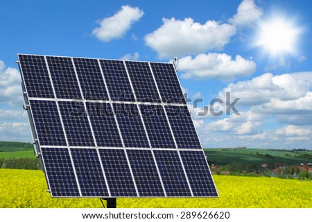 Solar panels on rapeseed field against sunny sky. Modern agriculture concept. - stock photo