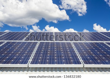 Solar panels on roof with cloudscape - stock photo