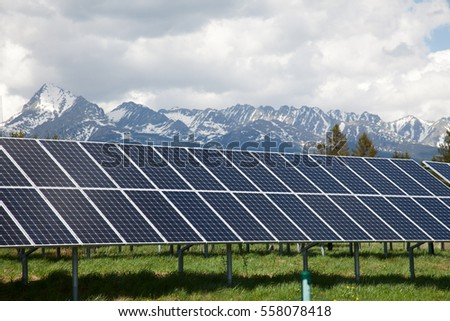 Solar panels on solar power station in Slovakia. Snow covered mountains and white clouds in the background. Green and environmentally friendly sources of energy.