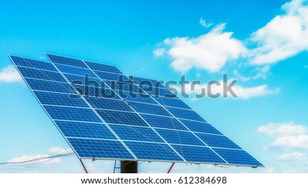 Solar panels on the green field in sunny weather. Vivid colorful image.