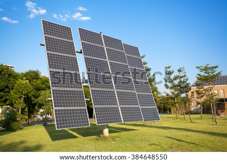 Solar panels on the green grass under blue sky with clouds.