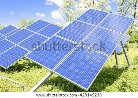 Solar panels placed on a countryside meadow. - stock photo