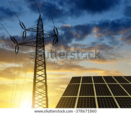 Solar panels with electricity pylon at sunset. Clean energy concept. - stock photo
