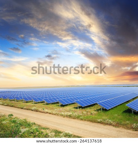 Solar panels with sunset's sky and road - stock photo