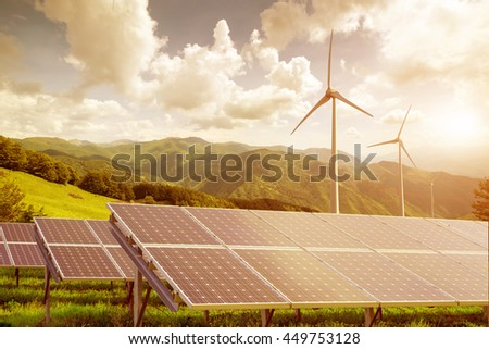 solar panels with wind turbines against mountains landscape against blue sky with clouds on sunset - stock photo