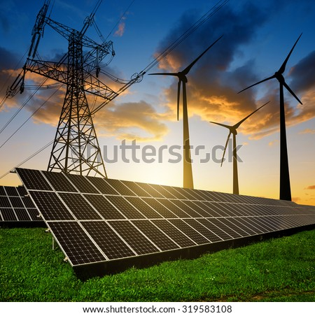 Solar panels with wind turbines and electricity pylon at sunset. Clean energy concept. - stock photo