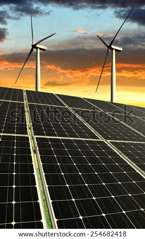 Solar panels with wind turbines in the setting sun  - stock photo
