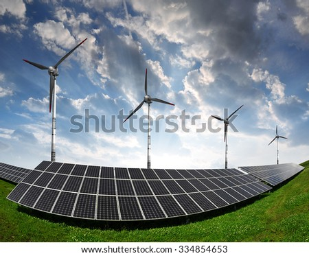 Solar panels with wind turbines in the setting sun. Concept of clean energy.