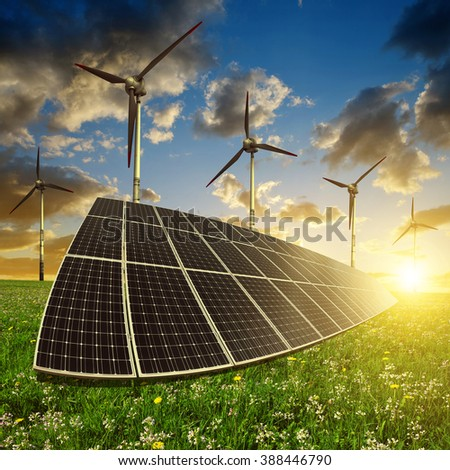 Solar panels with wind turbines in the setting sun. Concept of energy resources. - stock photo