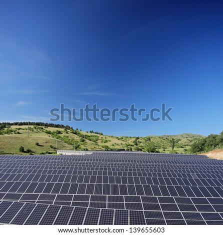 Solar photovoltaic cell panels on field under blue sky, Macedonia, shot with a tilt and shift lens