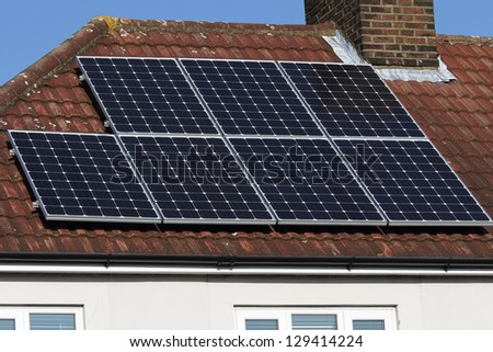 Solar photovoltaic panel array mounted on a tiled house roof against a blue sky - stock photo