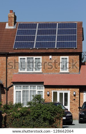 Solar photovoltaic panel array on house roof against a blue sky - stock photo