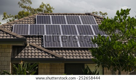 Solar photovoltaic panels installed on tiled roof - stock photo