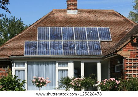 Solar photovoltaic panels mounted on a tiled house roof - stock photo