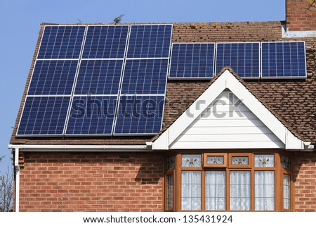 Solar photovoltaic panels on house roof against a blue sky - stock photo