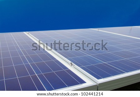 Solar photovoltaic panels on the roof of a house with a clear sky background - stock photo