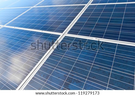 Solar photovoltaics panels field for renewable energy production with blue sky and clouds