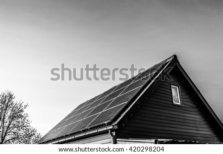 Solar power generation technology on house roof, alternative energy and environment protection ecology. Black-white photo. - stock photo