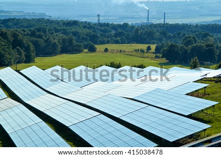Solar power panels on a green field surrounded by woods. The Smoking smokestack and the industrial landscape fading into the mist in the background. View from above.