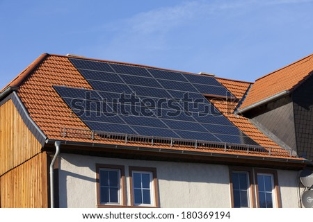 Solar power photovoltaic energy panels on tiled house roof - stock photo