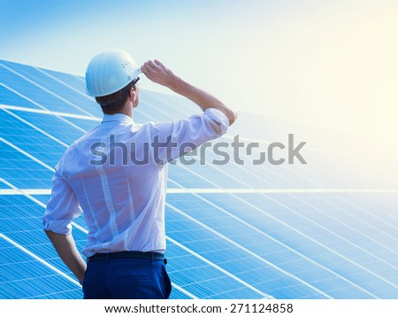 Solar power plant. Man standing near solar panels. Renewable energy. - stock photo