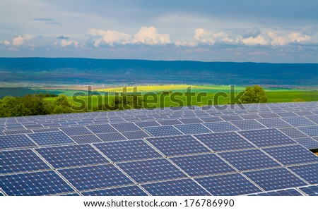 Solar power plant on the background of green fields and hills - stock photo