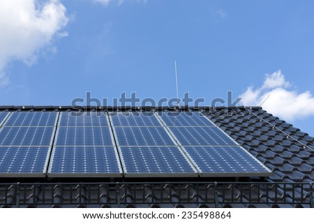 Solar power plant (photovoltaik) on the roof of a house in front of a blue sky. - stock photo