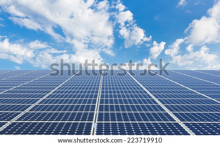 solar power station under blue sky, panels producing electricity  - stock photo