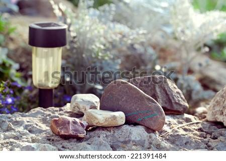Solar powered lamp on garden background. Selective focus on stones, toned photo  - stock photo