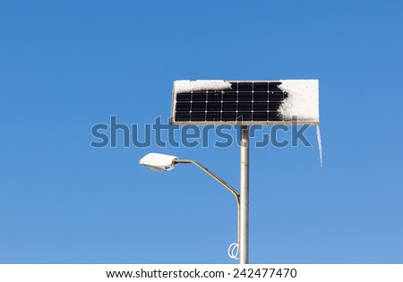 Solar powered street light with snow and ice on blue sky background - stock photo