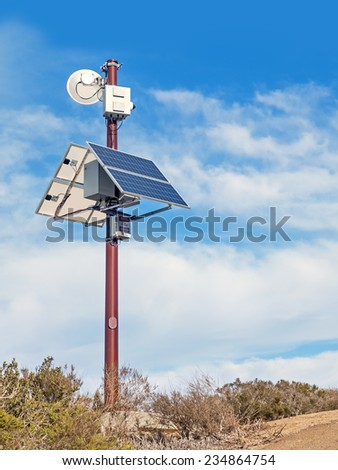Solar powered surveillance camera monitoring rural area. Video camera mounted on metal pole above solar panels. Blue sky and clouds background. Vertical composition.  - stock photo